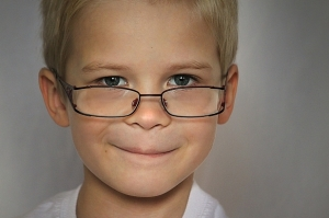 a boy wearing glasses and smiling